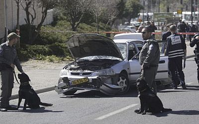 Police stand next to a car at the scene of a ramming attack in Jerusalem, March 6, 2015. (AP/Sebastian Scheiner)