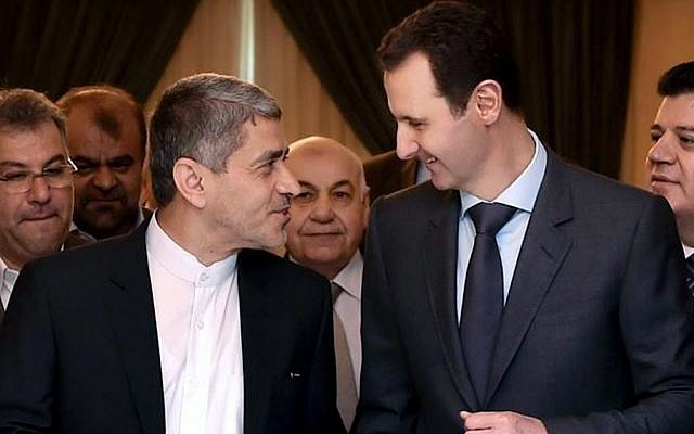 This photo released on the official Facebook page of the Syrian Presidency, shows Syrian President Bashar Assad, right, meeting with Iranian minister of economy and financial affairs, Ali Tayebnia, left, in Damascus, Syria, Monday, March 16, 2015. (Photo credit: AP)