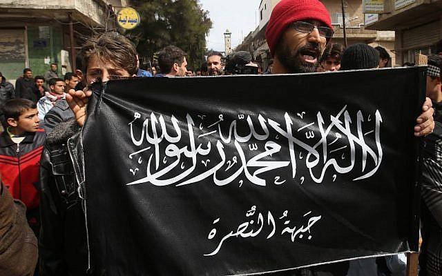 Anti-Syrian President Bashar Assad protesters hold the Jabhat al-Nusra flag, March 1, 2013 (AP Photo/Hussein Malla, File)