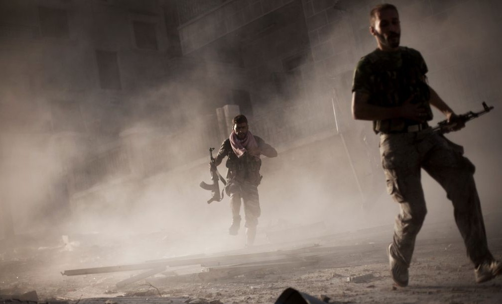 Free Syrian Army fighters run after attacking a Syrian Army tank during fighting in the Izaa district of Aleppo, Syria, on September 7, 2012. (AP/Manu Brabo, File)
