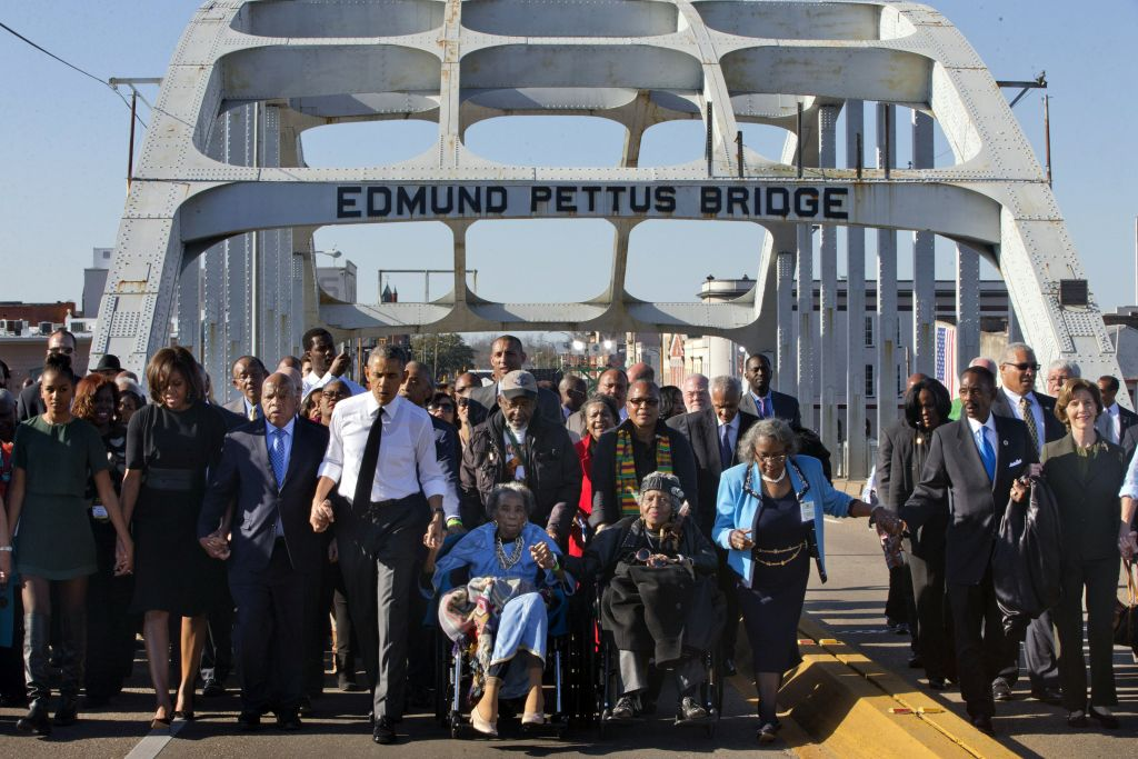 President Barack Obama, fourth from left, walks holding hands with Amelia Boynton Robinson, who was beaten during 'Bloody Sunday,' as they and the first family and others including Rep. John Lewis, D-Ga, left of Obama, walk across the Edmund Pettus Bridge in Selma, Ala,. for the 50th anniversary of the landmark event of the civil rights movement, Saturday, March 7, 2015. (AP Photo/Jacquelyn Martin)
