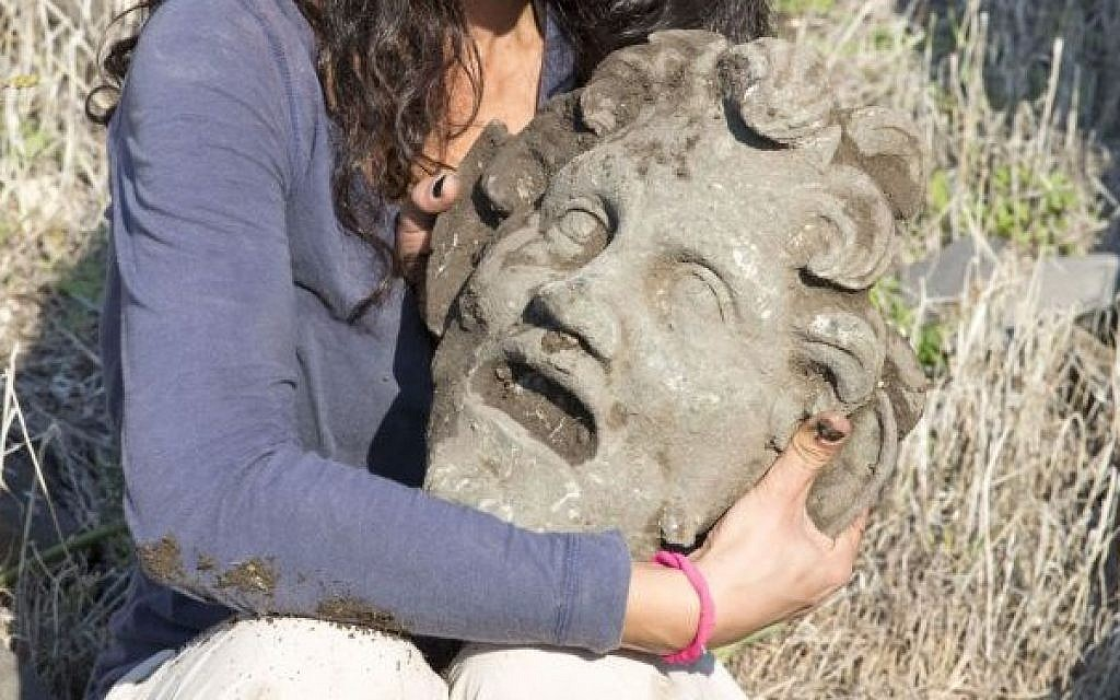 A Haifa University archeologist holding a massive bronze mask of the god Pan, found in early 2015 during digs in teh national park of Susita, in the north of Israel. (photo credit: Courtesy Haifa University)