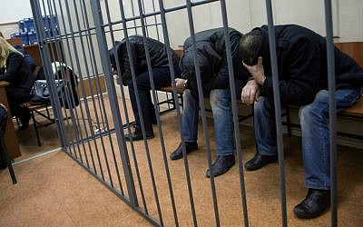 Three men, from the left: Tamerlan Eskerkhanov, Shagid Gubashev and Khamzad Bakhaev suspected of involvement in the killing of Boris Nemtsov sit in a court room in Moscow, Russia, Sunday, March 8, 2015. (AP Photo/Ivan Sekretarev)