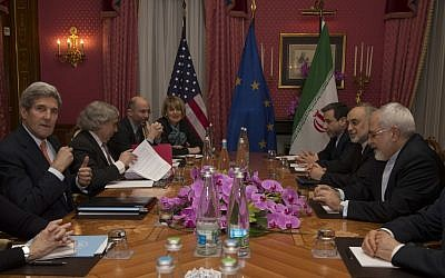 US Secretary of State John Kerry (left), during a meeting with Iran's Foreign Minister Mohammad Javad Zarif (seated opposite), over Iran's nuclear program, in Lausanne, Switzerland, on March 19, 2015. (photo credit: AP/Brian Snyder, Pool)