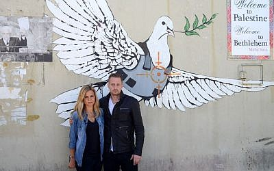 "Journalist Mariana Van Zeller, left, and chef Michael Voltaggio, hosts of Travel Channel's ""Breaking Borders,"" pose in front of an art piece showing a dove in a bulletproof vest by graffiti artist Banksy in Bethlehem. (Photo credit: AP Photo/Travel Channel)"