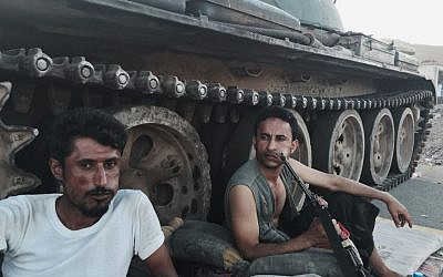 Members of a militia group loyal to Yemen's President Abed Rabbo Mansour Hadi, known as the Popular Committees, chew qat as they sit next to their tank, guarding a major intersection in Aden, Yemen, March 21, 2015 (AP Photo/Hamza Hendawi, File)