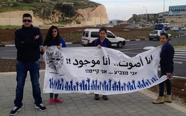 """At the entrance to Nazareth, a group belonging to the Zionist youth movement Hanoar Haoved Vehalomed hold up a sign reading """"I vote, therefore I exist."""" March 17, 2015. (Elhanan Miller)"""