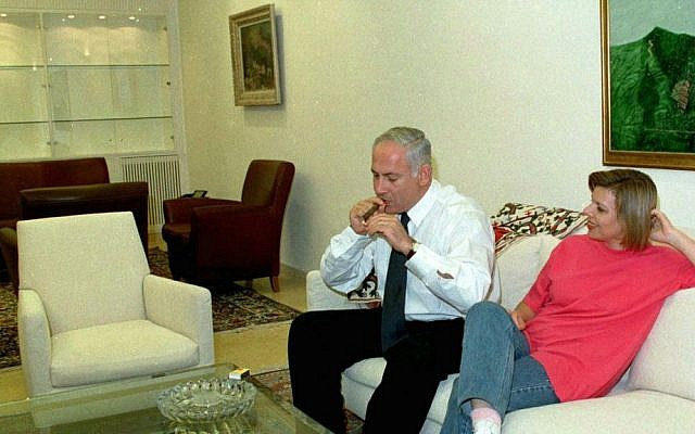 Netanyahu, sitting alongside his wife, Sara, enjoys a cigar on September 28, 1997, during his first term in office (AP Photo/Zoom 77)