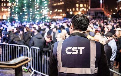 A Community Security Trust guard keeps watch over a Hanukkah celebration in 2014 (Blake Ezra Photography/JTA)