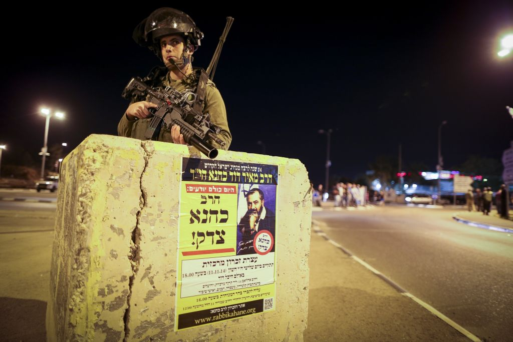 An Israeli soldier stands guard at the Gush Etzion junction, near the West Bank settlement of Alon Shvut, on November 10, 2014. Behind him is the Rami Levy supermarket, which has been praised as a haven of coexistence. (photo credit: Nati Shohat/Flash90)