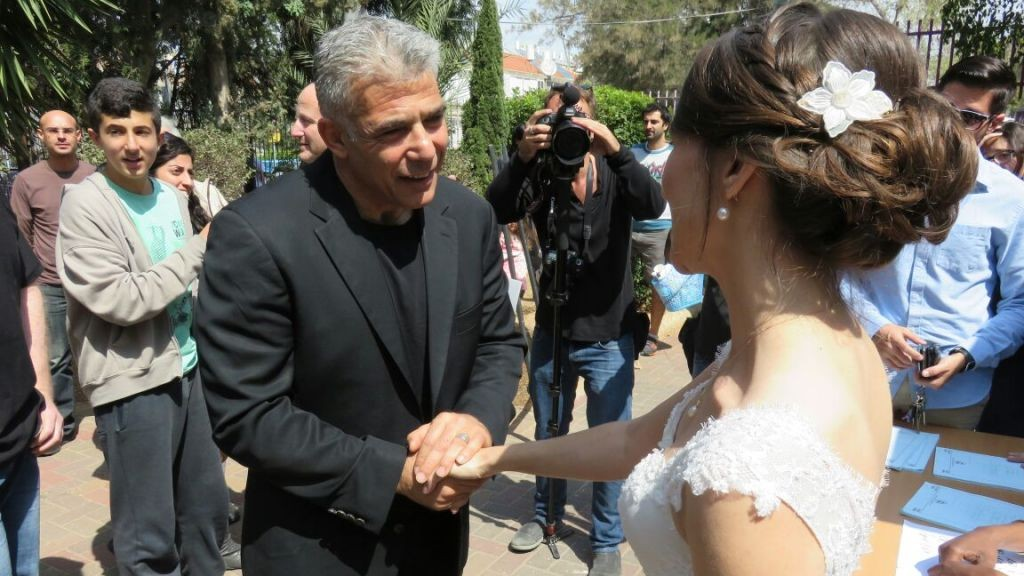 Yesh Atid leader Yair Lapid shakes hands with Victoria, who will marry Gary later on Tuesday. The couple both vote for Yesh Atid and went to vote on their way to their Huppah. (picture credit: Courtesy Yair Lapid)