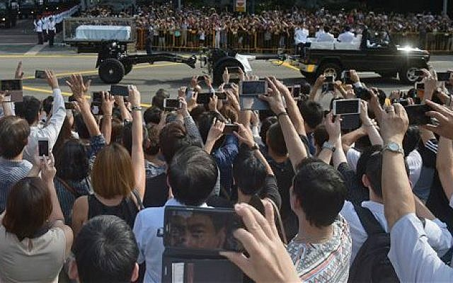 """Members of the public take pictures and shout """"Thank you, Mr Lee!"""" as the coffin of Singapore's founding father Lee Kuan Yew leaves Istana, or Presidential Palace on a ceremonial gun carriage to lie in state at parliament, Wednesday, March 25, 2015 in Singapore (photo credit: AP/Joseph Nair)"""