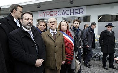 French Interior Minister Bernard Cazeneuve (2L) and French Jewish central Consistory President Joel Mergui (L) arrive on March 15, 2015 at the Hyper Cacher Jewish supermarket in Paris that became the site of a bloody hostage drama during a jihadist attack in January (photo credit: AFP/ KENZO TRIBOUILLARD)