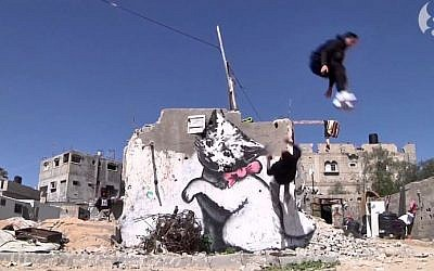 Gaza city parkour enthusiasts perform in front of graffiti by British artist Banksy in Gaza City. (screen capture: Youtube/The Guardian)