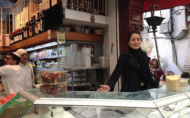 Shahar Levi sings amid Basher's cheeses in the shuk, at a promo for the June opera festival in Jerusalem (photo credit: Jessica Steinberg/Times of Israel)