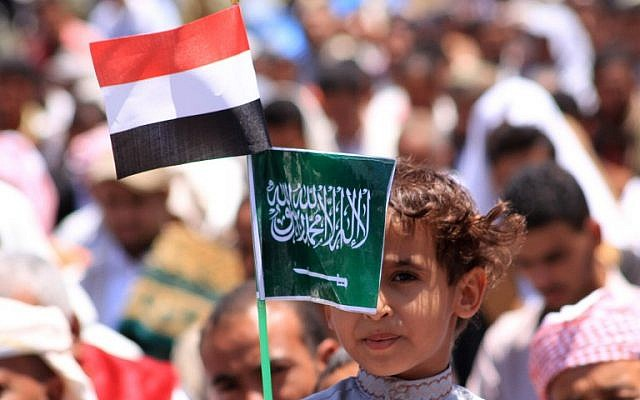 A Yemeni child holds Saudi (R) and Yemeni national flags during a demonstration in the strategic city of Taez on March 27, 2015, in support of the Saudi-led operation against Shiite rebels in the country (photo credit: AFP/STR)