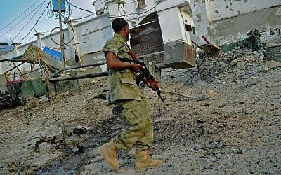 A soldier walks past at the scene of a car bomb attack and armed raid by Shebab terrorists on the Maka al Mukarama hotel in Mogadishu on March 27, 2015 (photo credit: AFP)