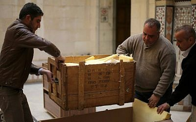 Damascus Museum employees wrap archaeological artifacts into boxes to protect them from being damaged on March 24, 2015, in the Syrian capital (photo credit: AFP PHOTO / JOSEPH EID)