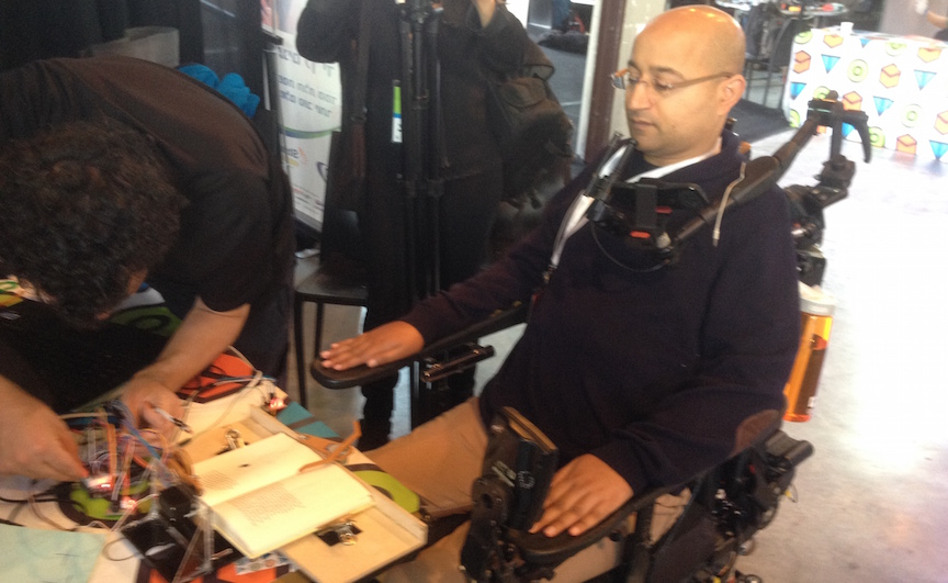 A wheelchair bound man uses an automatic book page turner developed at TOM:TLV (Photo credit: Courtesy)