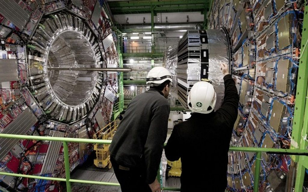 A Picture taken on February 10, 2015 shows workers in front of the CMS (Compact Muon Solenoid) Cavern at the European Organization for Nuclear Research (CERN) in Meyrin, near Geneva. The world's biggest particle collider was back in operation on April 5, 2015 after a two-year upgrade. (Photo credit: Richard Juilliart/AFP)