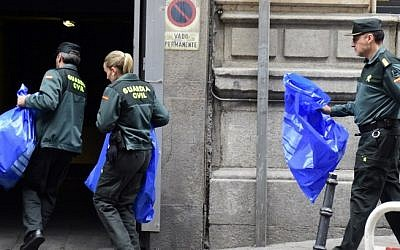 Spanish Civil Guard workers, carrying evidence and effects seized from people suspected of links to the Islamic State, arrive at the Spanish National Court in Madrid on April 10, 2015. (AFP/Gerard Julien)