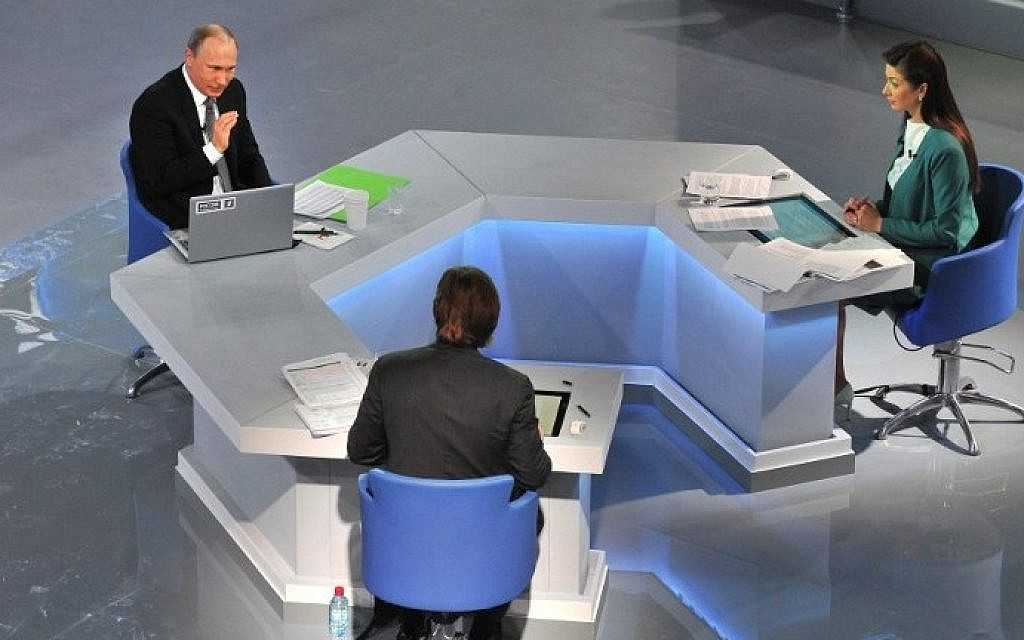 Russian President Vladimir Putin (L) gestures as he speaks during his annual televised phone-in with the nation in central Moscow on April 16, 2015. (photo credit: Mikhail Klimentyev/AFP/RIA Novosti)