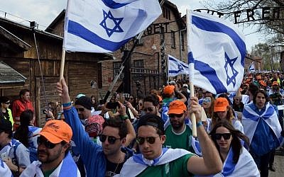 Participants wave Israeli flags at the main gate of the former Nazi German Auschwitz-Birkenau death camp during the 'March of the Living' at in Oswiecim, Poland on April 16, 2015. (Photo credit: Janek Skarzynski/AFP)