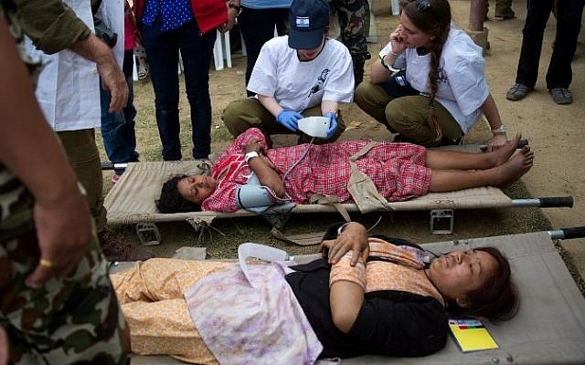 Injured Nepalese women are treated by Israeli Army medic soldiers at the Israeli field hospital on the second day of their mission in Kathmandu on April 29, 2015.  (AFP/ MENAHEM KAHANA)