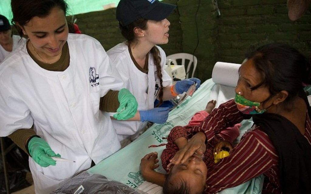 A nepalese baby is treated by Israeli Army medic soldiers at the Israeli field hospital on the second day of their mission in Kathmandu on April 29, 2015. (AFP/ MENAHEM KAHANA)