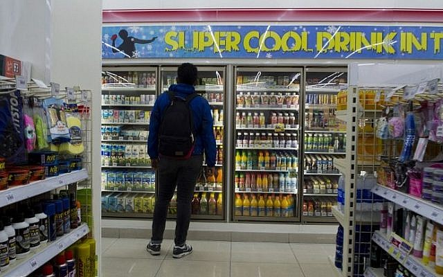 A customer looks at the cold drinks display at a mini mart in Jakarta on Apr. 10, 2015, where beers have been removed. Indonesia introduced a ban on small retailers selling most alcoholic drinks, the latest move to curb drinking in the world's most populous Muslim-majority country. (Photo credit: Romeo Gacad/AFP)
