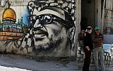 Palestinian refugees stand next to graffiti bearing a portrait of late Palestinian Authority president Yasser Arafat at the Ain Al-Helweh refugee camp, near the southern Lebanese city of Sidon, on March 16, 2015. (AFP/Joseph Eid)