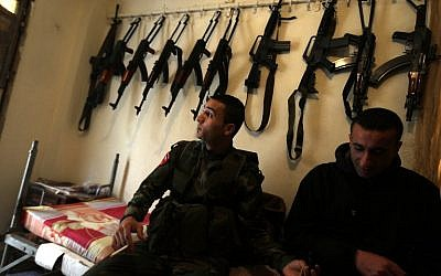 Palestinian militants sit at their post in the refugee camp of Ain Al-Helweh, near the southern Lebanese city of Sidon, on March 16, 2015. (photo credit: AFP / JOSEPH EID)