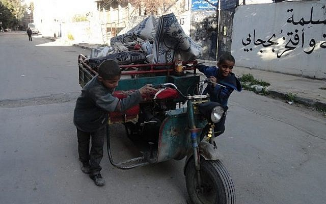 Boys pushing a cart in a street of Yarmouk Palestinian refugee camp, southern Damascus after around 2,000 people were evacuated from the camp after the Islamic State group seized large parts of it, April 4, 2015 (photo credit: AFP / RAMI AL-SAYED)