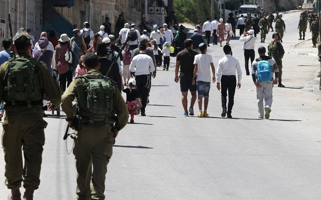 Israeli security forces guard settlers as they enter the Palestinian side of the West Bank city of Hebron to visit the tomb of Othniel Ben Kenaz, on April 5, 2015. (Photo credit: Hazem Bader/AFP)