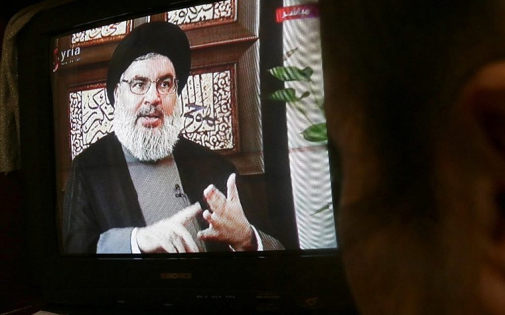 A Syrian watches an interview of Hassan Nasrallah screened on Syria's official television channel Al-Ikhbariya on April 6, 2015 in Damascus. (AFP/STR)