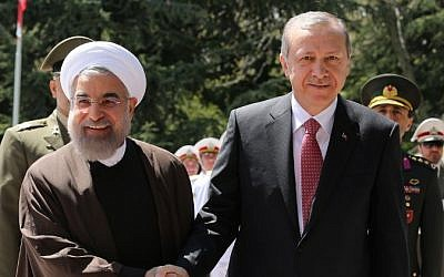 Iranian President Hassan Rouhani (left) shakes hands with Turkish President Recep Tayyip Erdogan (right) during an official welcoming ceremony at the Saadabad Palace in Tehran on April 7, 2015. (photo credit: AFP/Atta Kenare)