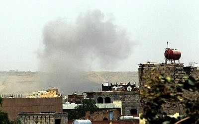 Smoke rises above the military academy in the Yemeni capital Sanaa on April 11, 2015, following an alleged air strike by the Saudi-led alliance on Shiite Houthi rebels camps. (photo credit: AFP/MOHAMMED HUWAIS)