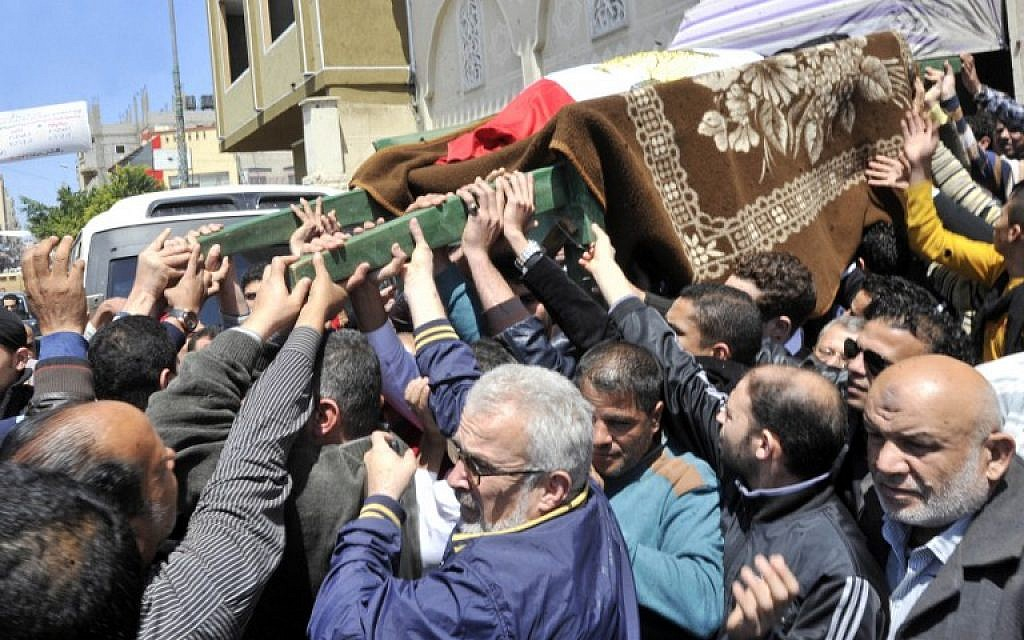 Egyptian relatives and mourners carry the body of police officer Amr Shoukry during his funeral in north Sinai's provincial capital of Al-Arish on April 13, 2015, after he was killed in a bomb attack targeting the Al-Arish police station the previous day. (photo credit: AFP/STR)
