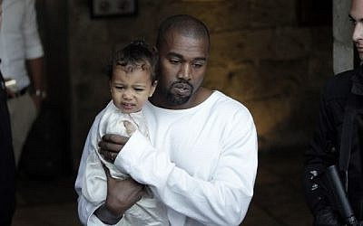 US rapper Kanye West, husband of US reality TV star Kim Kardashian, carries their daughter, North, following a reported baptism ceremony at the Armenian St. James Cathedral in Jerusalem's Old City on April 13, 2015. (photo credit: AFP/Ahmad Gharabli)