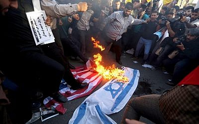 Iranians burn and stomp on Israeli and American flags during a demonstration against the Saudi-led coalition's Operation Decisive Storm against the Houthi rebels in Yemen, outside the Saudi Embassy in Tehran, April 13, 2015. (AFP/Atta Kenare)