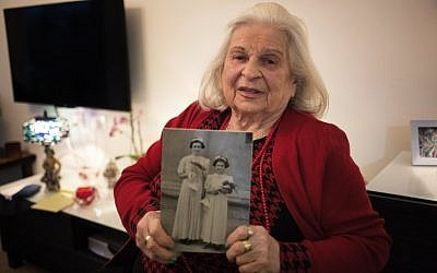 Suzanna Braun, who experienced the horrors of the Holocaust, holds a photo of herself and her sister, Agi, as she speaks during an interview in Shoresh, a small village west of Jerusalem on April 14, 2015, ahead of Israel's Holocaust memorial day. (photo credit: AFP PHOTO / MENAHEM KAHANA)