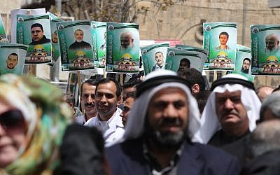 Portraits of members of the Hamas terror group who are jailed in Israeli prisons, seen during a demonstration in their support in the West Bank city of Hebron, on April 15, 2015. (photo credit: AFP PHOTO/HAZEM BADER)