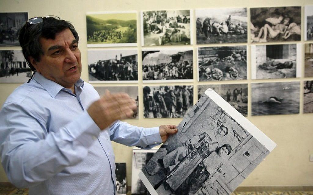 Armenian Serop Sahagian, the head of the Homenetmen Club, hang pictures to be displayed in an exhibition marking the 100th anniversary of the mass killings of Armenians under the Ottoman Empire in 1915, on April 17, 2015 in the Armenian Quarter in Jerusalem's Old City. Armenians around the world will mark on April 24, 2015 the centenary of the World War I-era mass killings of their kin by Ottoman Turks in what they insist was a genocide -- a term fiercely rejected by Turkey. (photo credit: AFP PHOTO / GALI TIBBON)