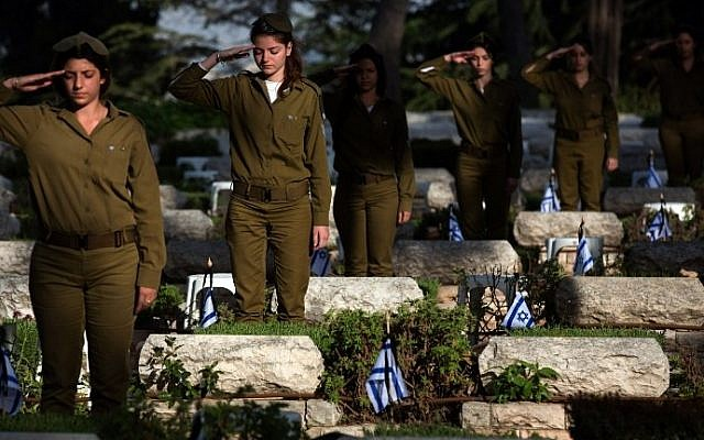 Israeli soldiers salute after placing the national flag on the graves of Israeli soldiers at the Mount Herzl military cemetery in Jerusalem on April 19, 201 three days ahead of the Memorial Day honoring the fallen soldiers. Israel will mark the Remembrance Day on April 22,to commemorate over 23,320 fallen soldiers since 1948, just before the celebrations of the 67th anniversary of its creation. (Photo credit: Menahem Kahana/AFP)
