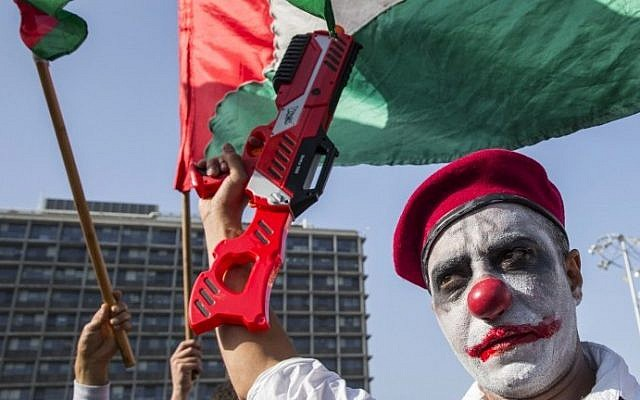 An Arab Israeli man, with his face painted, holds a plastic gun during a rally against the demolition of Arab homes across the country at Rabin Square in Tel Aviv on April 28, 2015. photo credit: AFP PHOTO / JACK GUEZ)