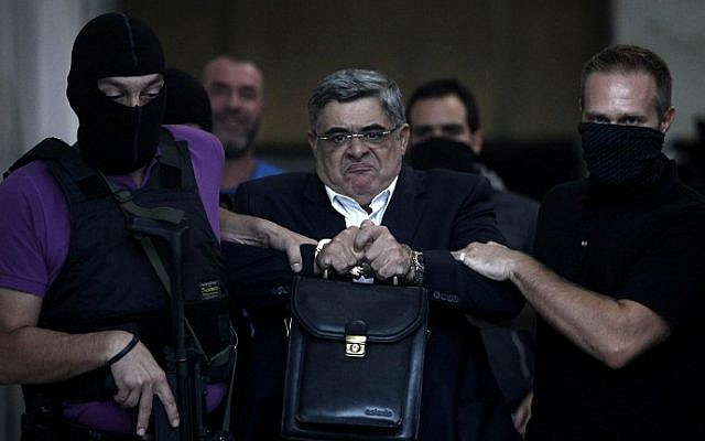 A file picture taken on September 28, 2013 shows the leader of ultra-right wing Golden Dawn party Nikos Michaloliakos being escorted by masked police officers to the prosecutor from the police headquarters in Athens, Greece. (AFP photo/Angelos Tzortzinis)