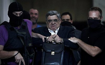 File picture shows the leader of ultra-right wing Golden Dawn party Nikos Michaloliakos being escorted by masked police officers to the prosecutor from the police headquarters in Athens, September 28, 2013. (photo credit: AFP/ANGELOS TZORTZINIS)
