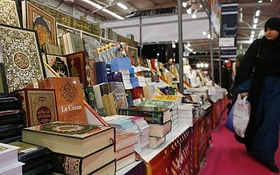A woman walking past a stands displaying the Muslim Quran and other literature during the 32nd Annual Meeting of France's Muslims, at Le Bourget Exhibition center, north of Paris, April 3, 2015 (Photo credit: Thomas Samson/AFP)