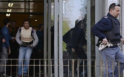 Police officers run at the entrance to Milan's court during a shooting on April 9, 2015. An armed man, identified as Claudio Giardiello, believed to be a defendant in a bankruptcy case shot two people dead, including a judge, on the third floor of the Milan court. (Photo credit: Olivier Morin/AFP)