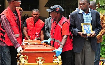 A relative holds a portrait of his relative as he watches her coffin being rolled out by Kenya Red Cross personnel at Chiromo funeral parlor in Nairobi, April 9, 2015. (photo credit: AFP/STRINGER)